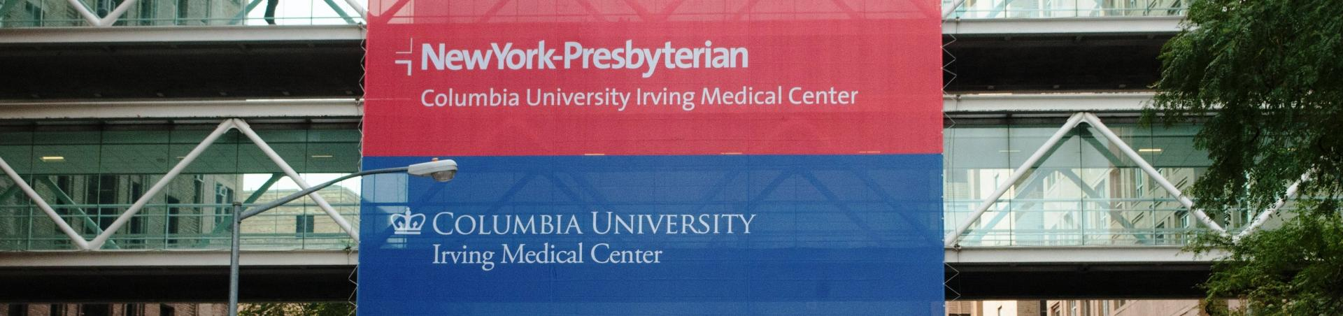 Signs for NYPH and CUMC hanging from buidling skywalk