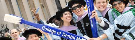 Graduating students holding a large toothebrush showing the College of Dental Medicine logo on it.